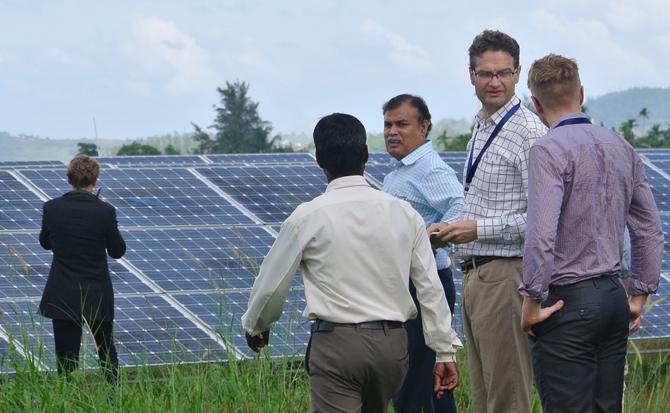 Five men in front of solar panels. Photo.