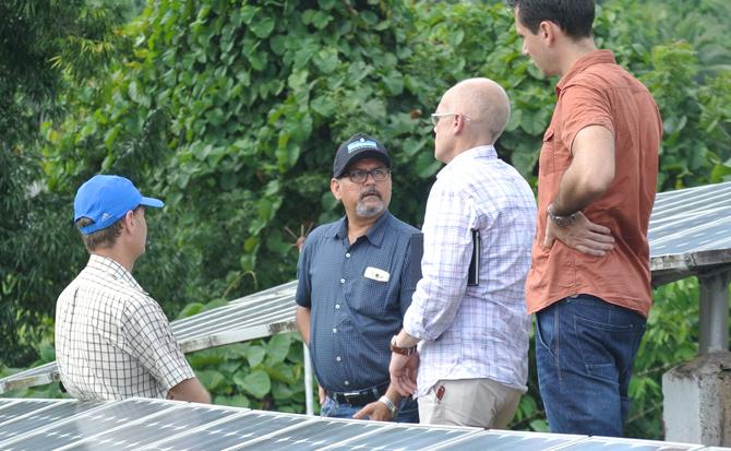 Four men standing next to solar panels. Photo.
