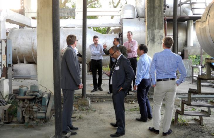 Seven men next to a technical installation outdoors. Photo.