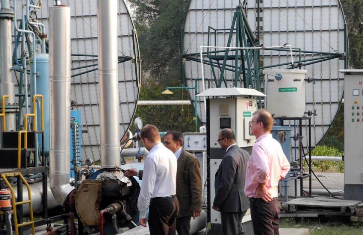Four men looking at a technical installation outdoors. Photo.