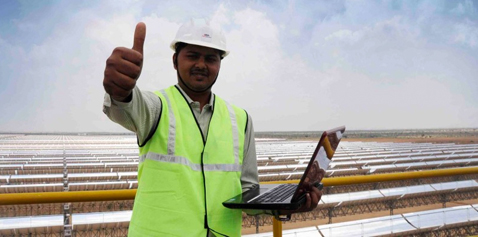 """A man next to a solar power plant, doing a """"thumbs up"""". Photo."""