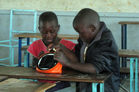Two boys inspecting a product. Photo.