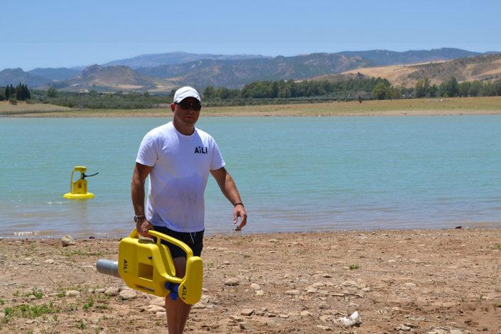 Henrik Johansson carrying a yellow water pump. Photo.
