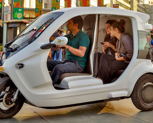 Three people in a small electric vehicle. Photo.