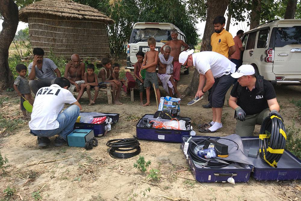 Three men handling technical equipment, children and villagers watching. Photo.