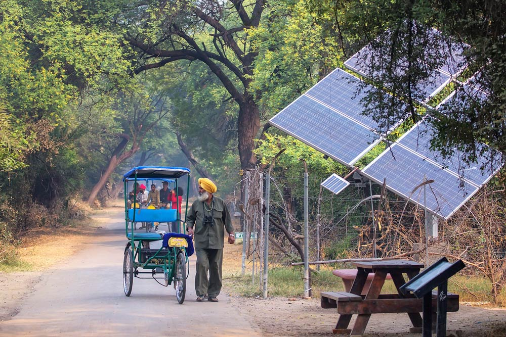 Solar panels in rural area, people and rickshaws. Photo.