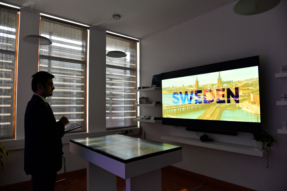A standing man watching a big screen on a wall. Photo.
