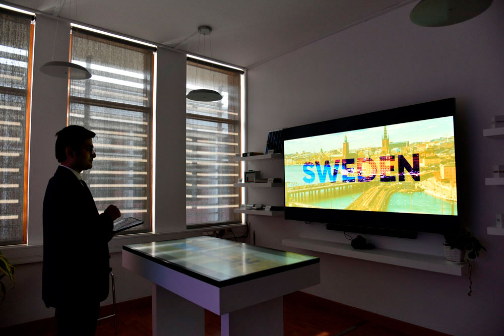 A standing man looking at a big screen. Photo.