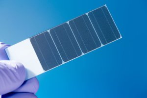 Fingers holding small piece of solar cells. Photo.