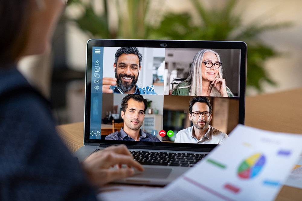 Online meeting: four people on a computer screen. Photo.