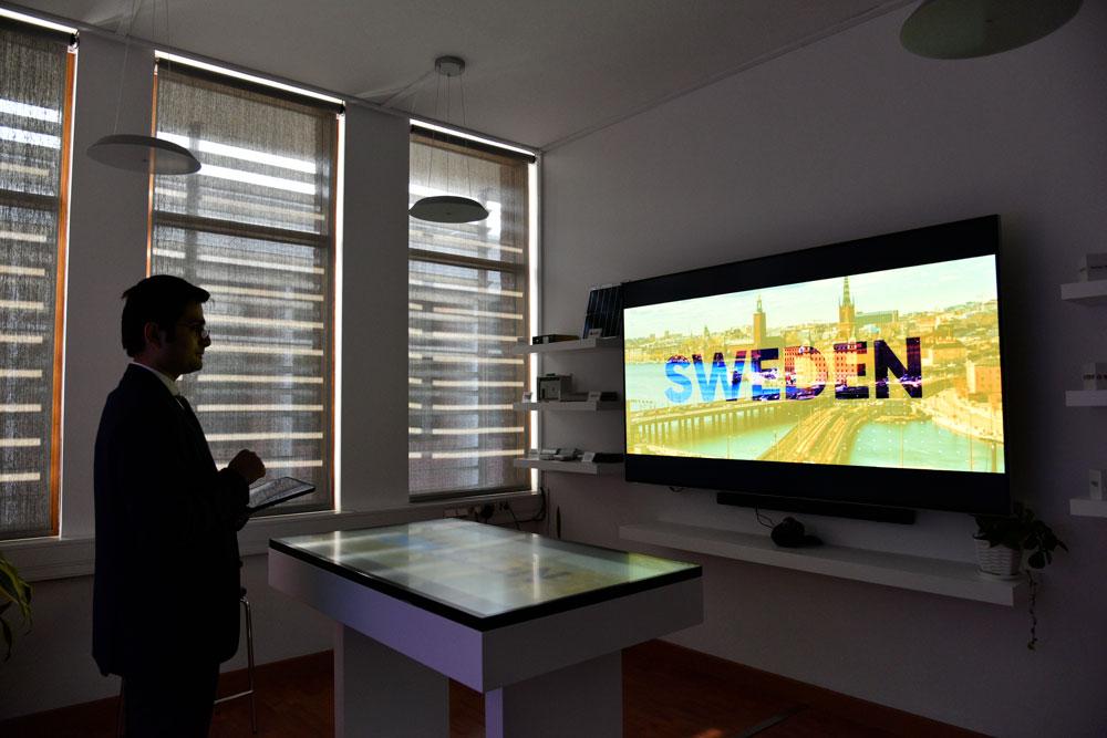 A man watching a big screen in the showroom. Photo.
